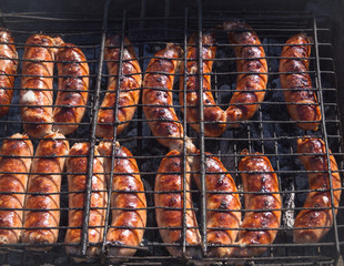 Meat sausages are fried on smoke. Top view.
