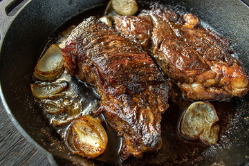 grilled beef flanks with onions in cast iron pan
