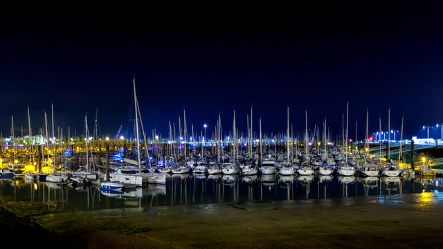 White sailing boats at harbour at night against dark blue sky