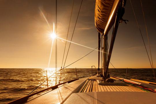 Sailing towards sunset at open sea