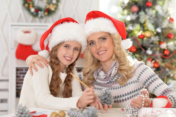 Portrait of cute happy young mother and daughter preparing for Christmas