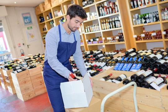 wine merchant unpacking box of wine