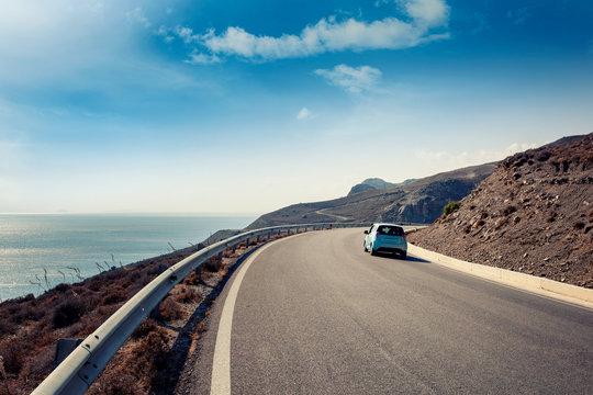 Blue small car rides along a serpentine mountain road along the sea, Kos island, Greece