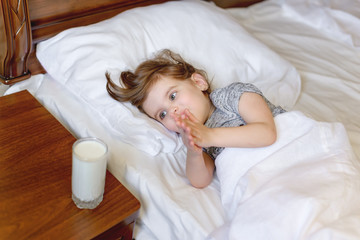 Child is awake, lying in bed reaching for milk, soft white linen. Concept of a healthy lifestyle. Vitamins health.