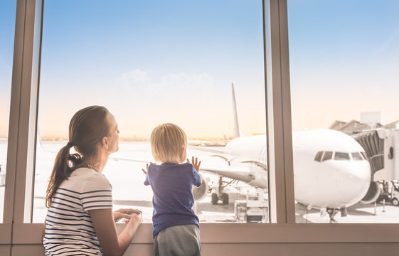 Mother and son at airport boarding terminal looking out window at airplane. Family travel.