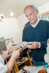 Customer passing sandal to cobbler