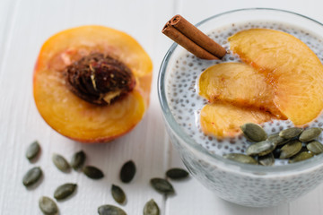 Half peach, cinnamon stick, pumpkin seeds and Chia seed pudding on wooden white table.
