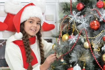 Cute little girl in Santa hat decorating Christmas tree