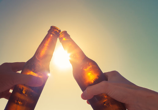 Hands toasting beer on sunset background. Party and celebration concept.