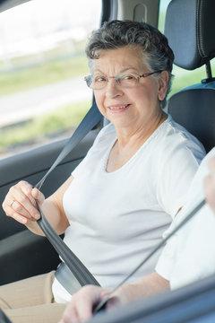 Elderly lady putting on her seatbelt