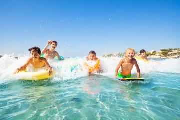 Happy friends swimming in the sea on body boards
