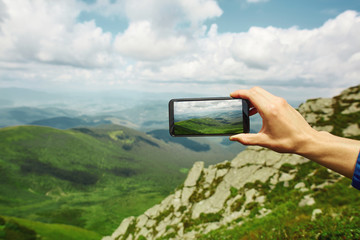 man photographing mountain landscape by the phone