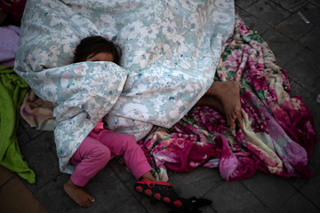 Girl lies waiting for parents to awake as they rest amid thousands from Central America en route to the United States in Huixtla, Mexico