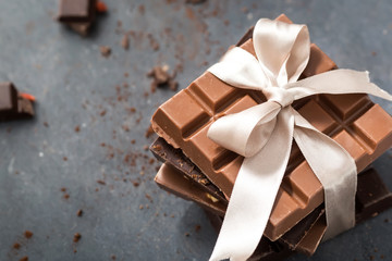 Chocolate bars with beige bow on a grey background