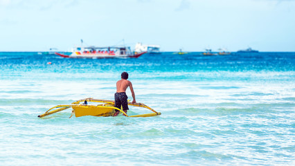 A man with a boat near the shore, Boracay, Philippines. Copy space for text. Back view.
