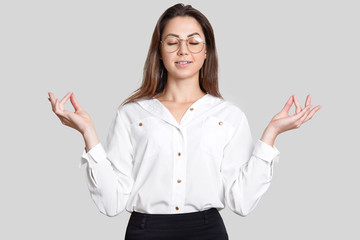 Photo of peaceful calm young woman holds hands in mudra gesture, tries to relax and concentrate before important business meeting, dressed in formal clothes, spectacles, isolated on white wall