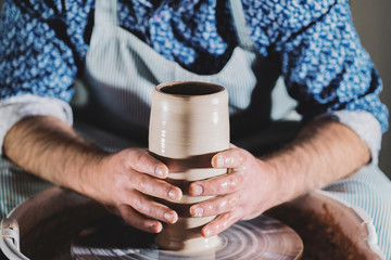 View of man making pot on pottery wheel. Potter shapes the clay product - vase - with professional tools, top view. Small business owner working in workshop