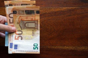 Hand holding euro banknotes. Top view with copy space