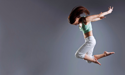 Woman jump. Beauty girl dance on grey background
