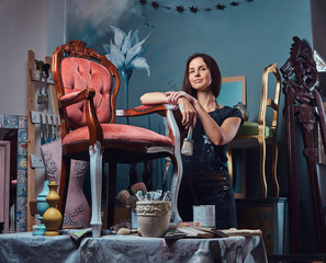 Female artist holds paintbrush and leaning on a vintage chair in workshop.