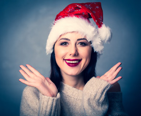 Portrait of a style brunette woman in christmas hat on grey background
