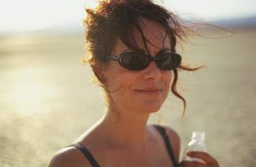 Young woman wearing sunglasses and holding a water bottle while outdoors.