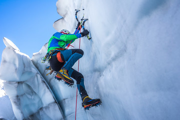 Epic shot of an ice climber climbing on a wall of ice. Mountaineer, climber or alpinist on an adventure extreme ascent with ice axe and crampons. Alpine extreme climbing on a serac or creavasse. Wall mural