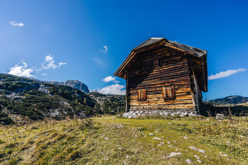 An old rustic mountain cabin or hut made of dark brown wood. Vintage mountain hut in the alpine mountain landscape. Summer blue sky, green grass.