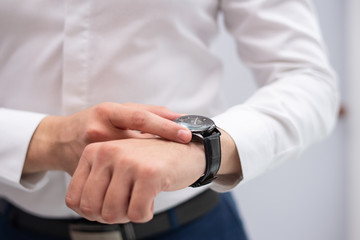 Close-up of businessman looking at his modern wristwatch. Caucasian manager checking time. Time and punctuality concept