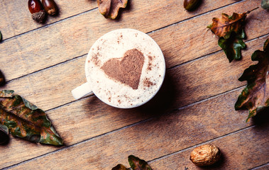 photo of the cup of coffee and fallen leaves on the brown wooden background