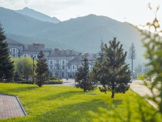 Beautiful green glade with trees on the background of the hotel and the mountains of Krasnaya Polyana Sochi 09/29/2018