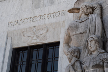 Text and an eagle carved into marble above the entrance to the Oregon State Capitol building in Salem, part of a marble relief carving representing white settlers in the foreground.