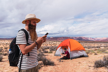 Traveler using smartphone near tent and friend