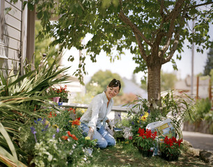 Young woman happily tending to her outdoor garden.