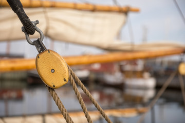 Pulley for sails and ropes made from wood on an old sail boat, with sail and other boats out of focus in the background.