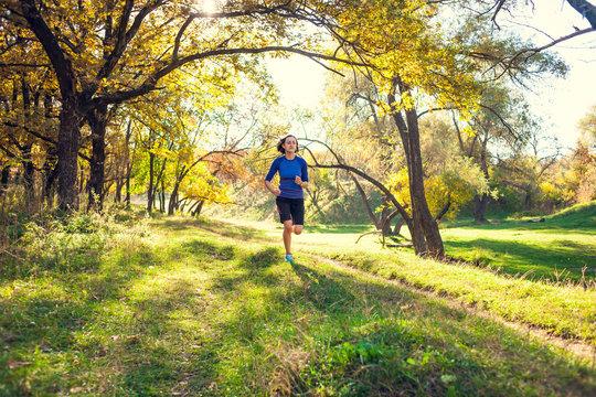 The girl runs through the autumn park.