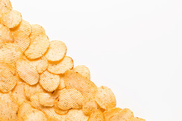 Crispy potatoes chips isolated on white background. Food background. Potato chips lying diagonally from top to bottom from left to right on a white table