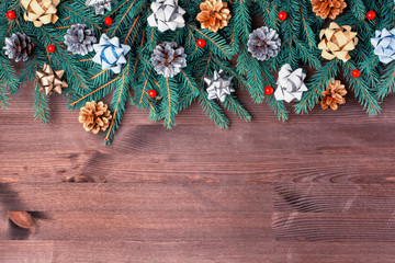 Christmas composition on a dark background. Spruce branches, bows, artificial red berries and gold and silver cones. Copy space.