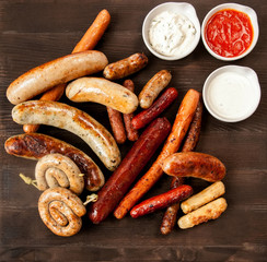 Assorted fried sausages on a wooden board
