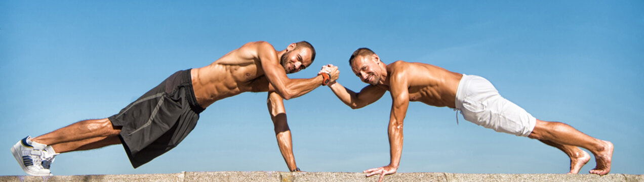 Men hold ab plank. Muscular men do sport. Health care. Success in sport and health activities. Developing muscular strength and power. Success is the result of perfection