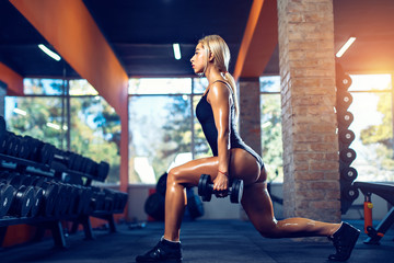 Sport, bodybuilding, lifestyle concept. Fit young woman in great shape lifting barbells looking down, working out in a gym. Sporty sexy woman doing squat workout with dumbbell. Strong legs