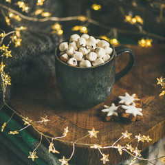 Christmas or New Year winter hot chocolate with marshmallows in dark mug over wooden board served in bed with holiday light garland, blanket and gray sweater, selective focus, square crop
