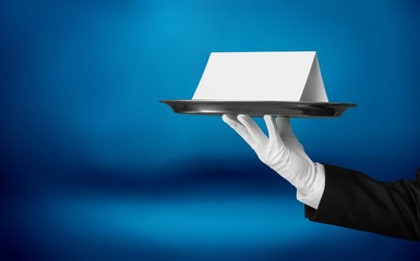 Elegant waiter hand in white glove holding  plate with note