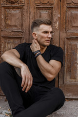 Stylish handsome young man with hairstyle in fashionable black t-shirt sitting near a wooden vintage door
