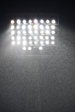 Raining in the stadium and spotlight.
