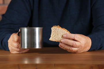 Poor elderly woman with piece of bread and metal mug at table, focus on hands