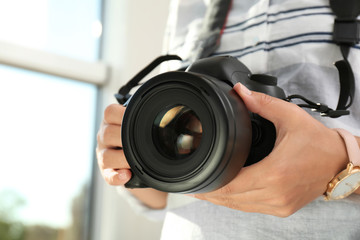 Female photographer with professional camera on blurred background, closeup