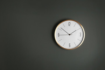 Stylish analog clock hanging on gray wall, space for text. Time of day
