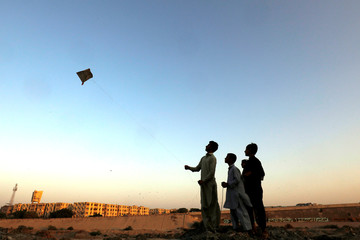 A boy with friends, flies a kite along the dry bed of Lyari River in Karachi,