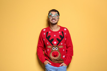 Young man in Christmas sweater with party glasses on color background